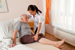 caregiver supporting an elderly man on bed