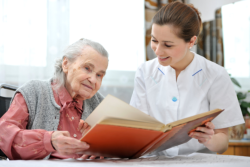 elderly woman with her caregiver reading a book
